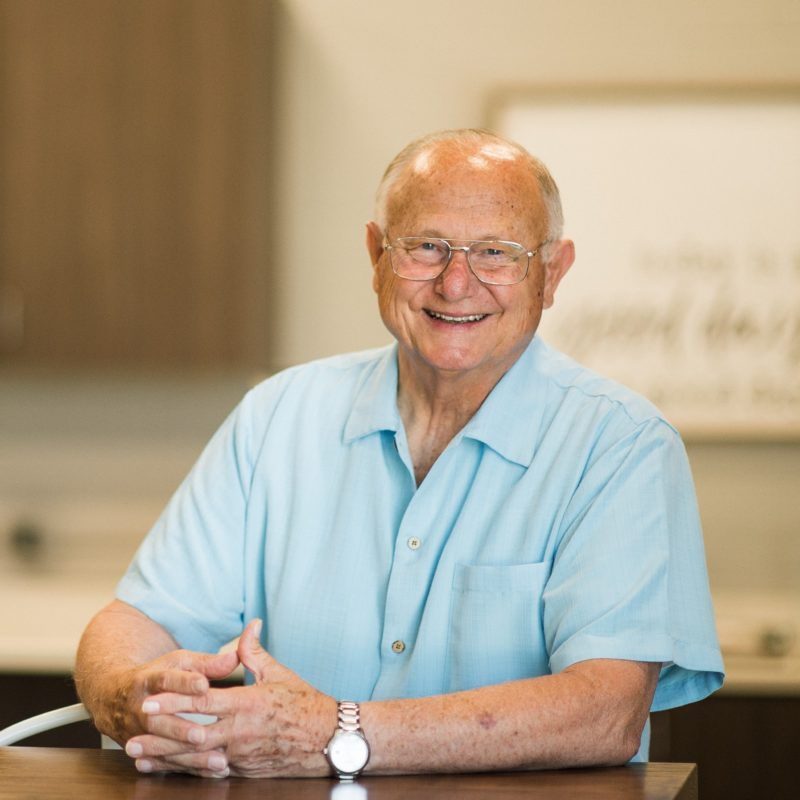 Friendly, smiling older man wearing glasses and blue short sleeved button front shirt placing hands on countertop