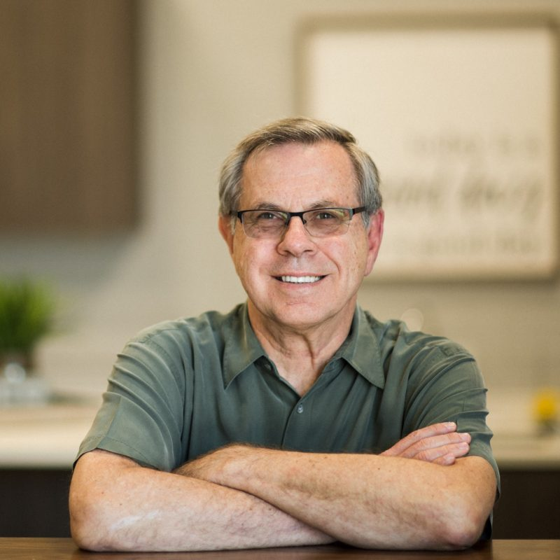Smiling older man with glasses and olive polo shirt leaning crossed arms onto counter
