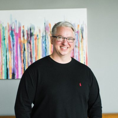 Smiling man with white hair, glasses and black t-shirt standing relaxed in front of a colorful painting